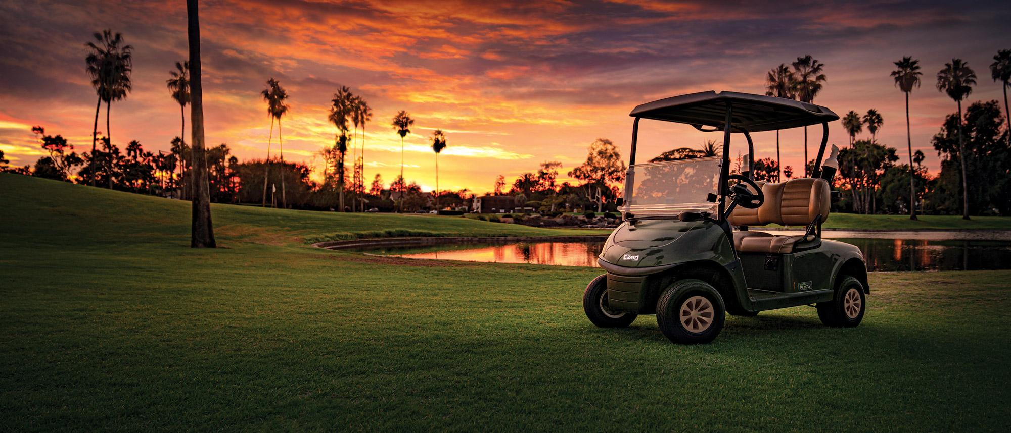 Golf cart sitting still on a golf course in the sunset